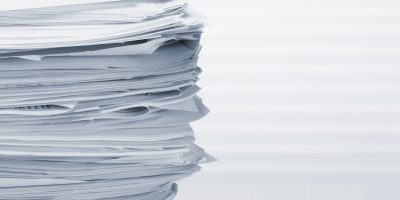Stack of paper documents on office table. Toned